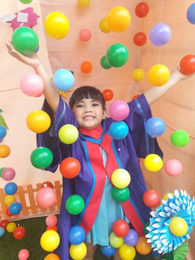 Portrait of smiling girl with colorful balloons hanging against wall