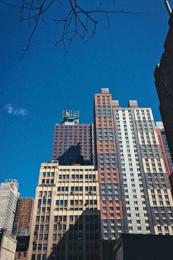 Low angle view of office buildings against blue sky
