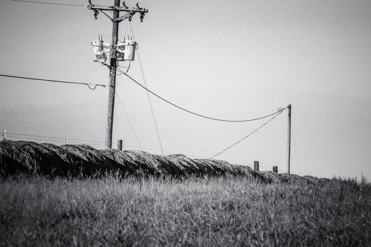 Hay Bale Cable Clear Sky Connection Day Electricity  Electricity Pylon Field Fuel And Power Generation Grass Low Angle View Modern Farming Nature No People Outdoors Power Line  Power Supply Sky Technology Telephone Line