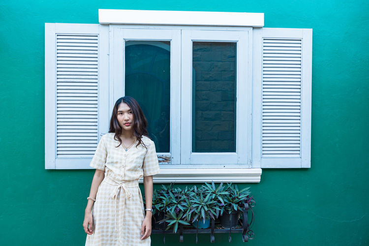 Woman standing against window on wall