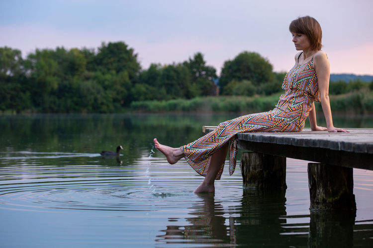 Side view of woman sitting by lake