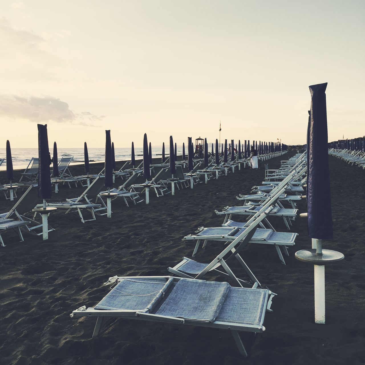 Parasols And Deck Chairs At Beach Against Sky During Sunset