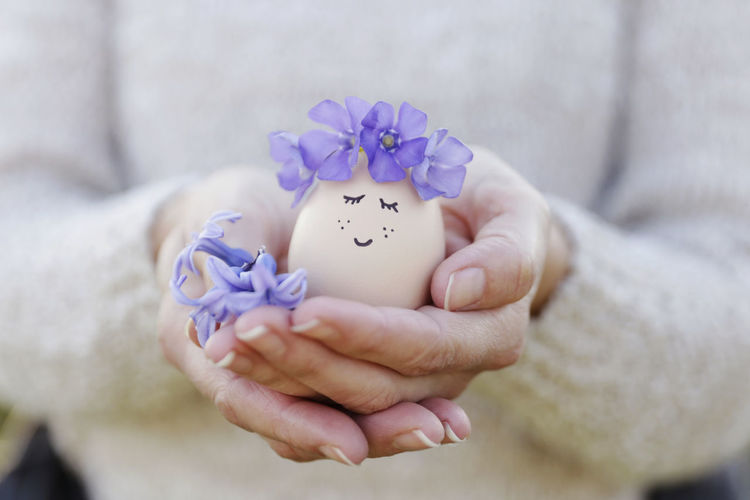 Close-up of hand holding purple flower