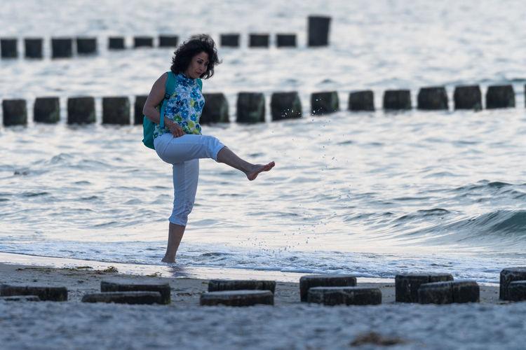 Full length of woman splashing on beach
