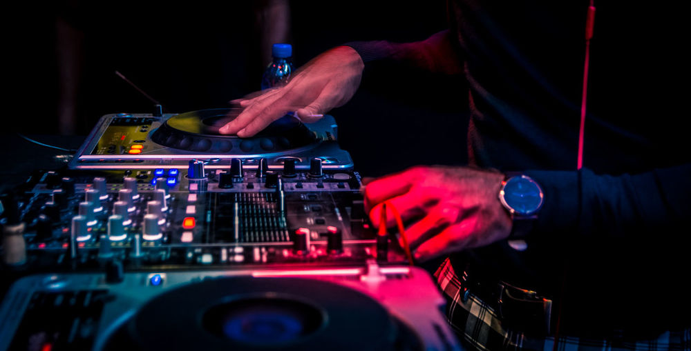 Midsection of dj playing music at nightclub