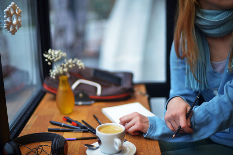 Midsection of woman working with coffee on table