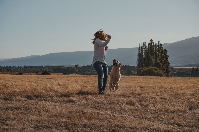 Full length of woman with dog on field