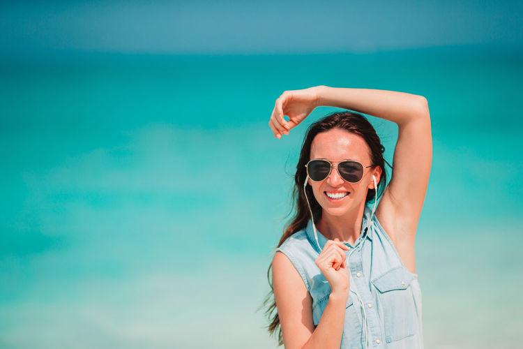 Cheerful woman listening music at beach