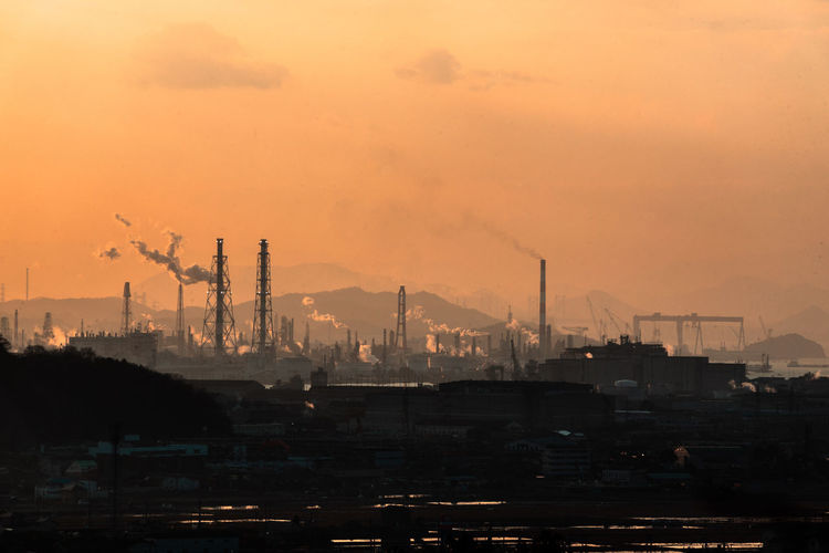 Factory Industry Smoke Stack Building Exterior Architecture Pollution Environmental Issues Sky Built Structure Environment Smoke - Physical Structure Sunset Orange Color No People Air Pollution Fuel And Power Generation Emitting Nature Chimney Outdoors Atmospheric Fumes Ecosystem  Industrial District Smog