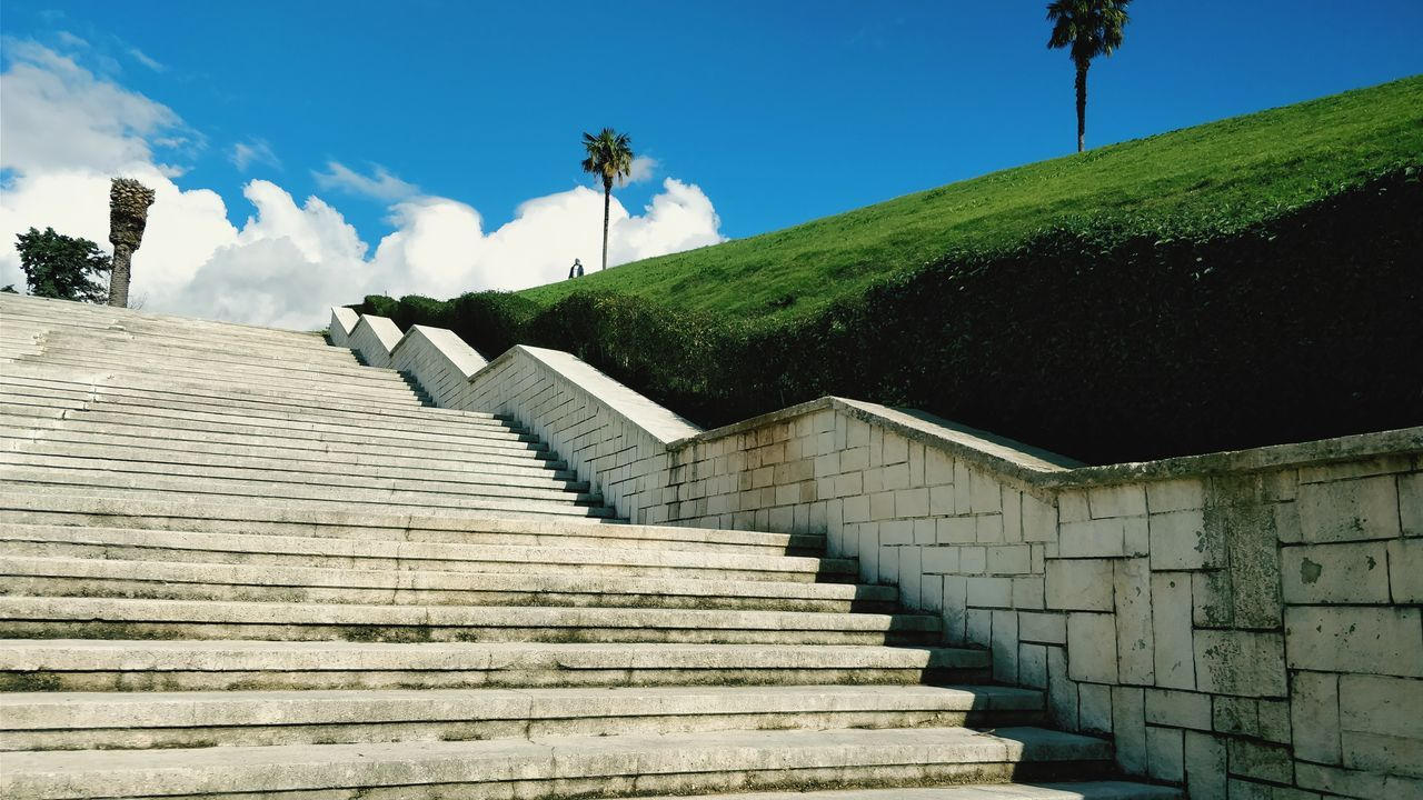 sky, architecture, staircase, low angle view, built structure, steps and staircases, cloud - sky, plant, tree, nature, day, no people, outdoors, sunlight, building exterior, wall, the way forward, direction, blue, moving up