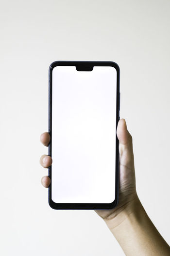 Low angle view of hand holding smart phone against white background