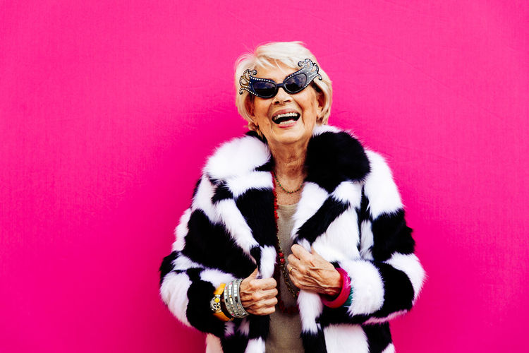 Portrait of senior woman laughing while standing against pink background