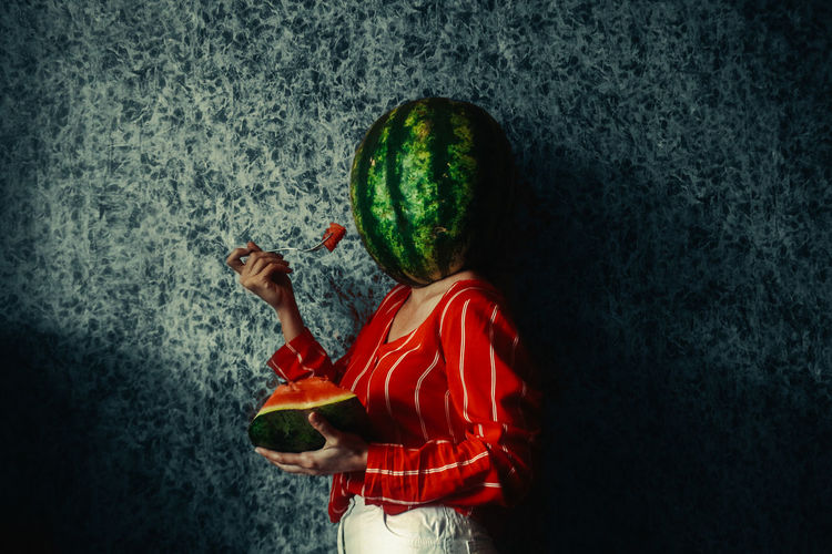 Rear view of girl holding fruit