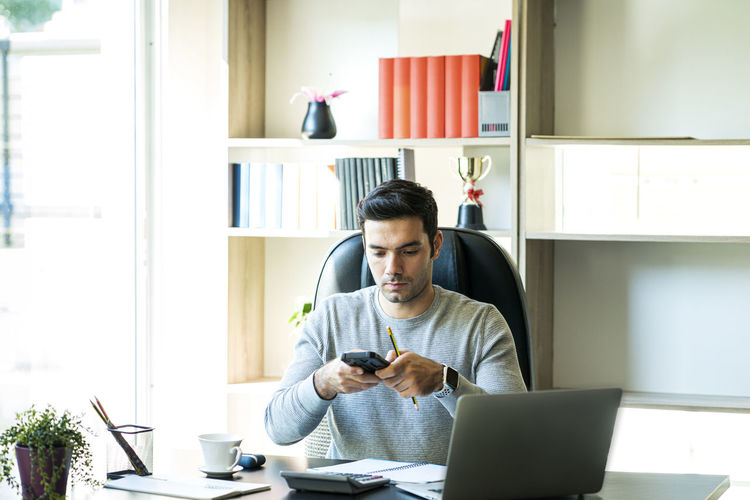 Businessman using mobile phone while sitting at office