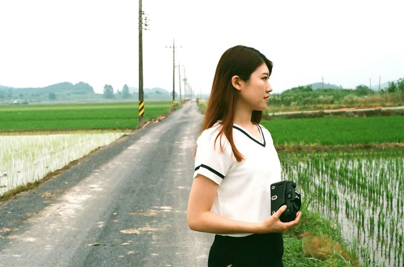 Beautiful Woman Holding Camera While Standing On Road Amidst Rice Paddy
