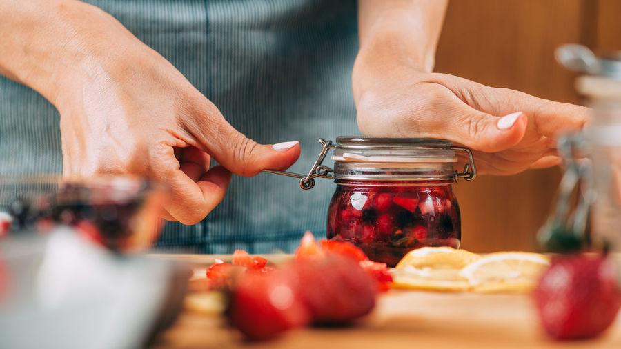 Fruit fermentation. woman holding jar with fermented fruit.