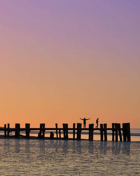 Silhouette wooden posts in sea against orange sky
