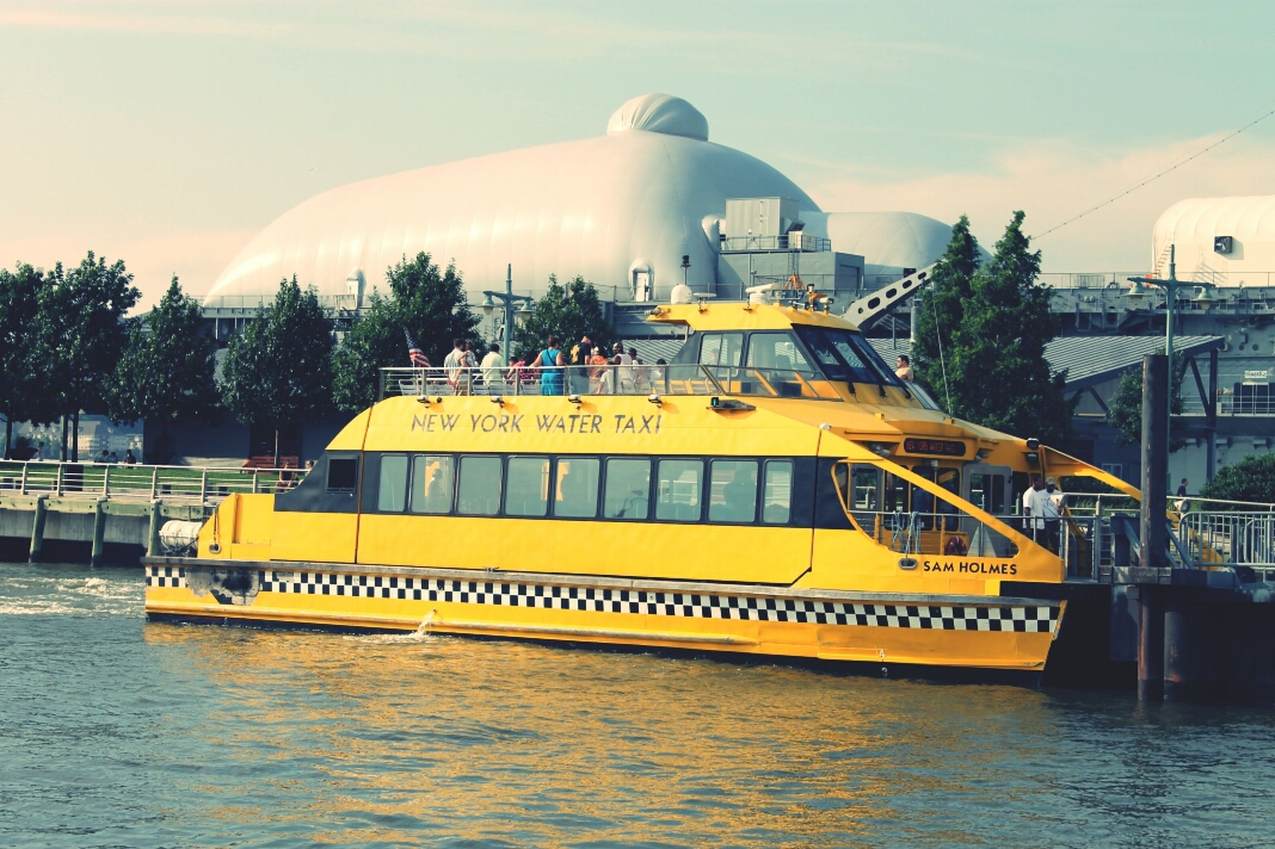 water, architecture, built structure, transportation, building exterior, mode of transport, yellow, nautical vessel, waterfront, sky, travel, boat, river, outdoors, incidental people, tree, rippled, sunlight, reflection, day