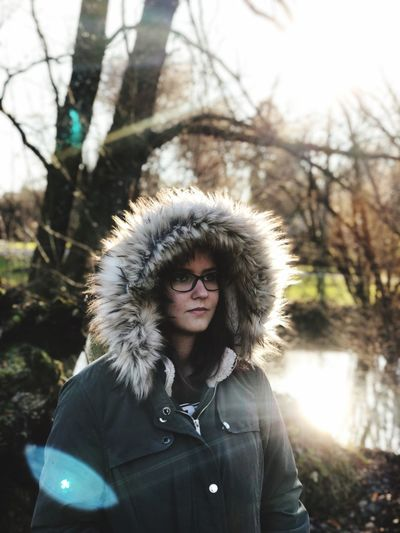 Close-Up Of Young Woman Wearing Fake Fur Against Bare Trees