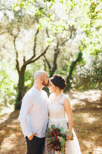 Man kissing woman while standing in forest