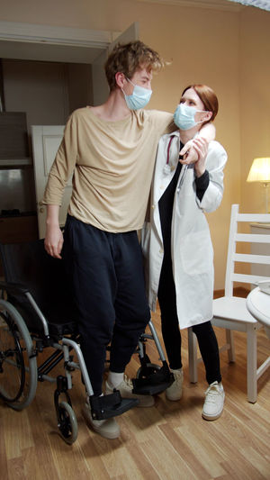 Young man with woman standing on floor at home