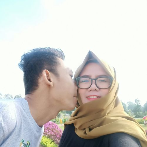 Portrait of young couple kissing against sky