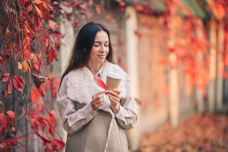 Woman standing by maple leaf during autumn