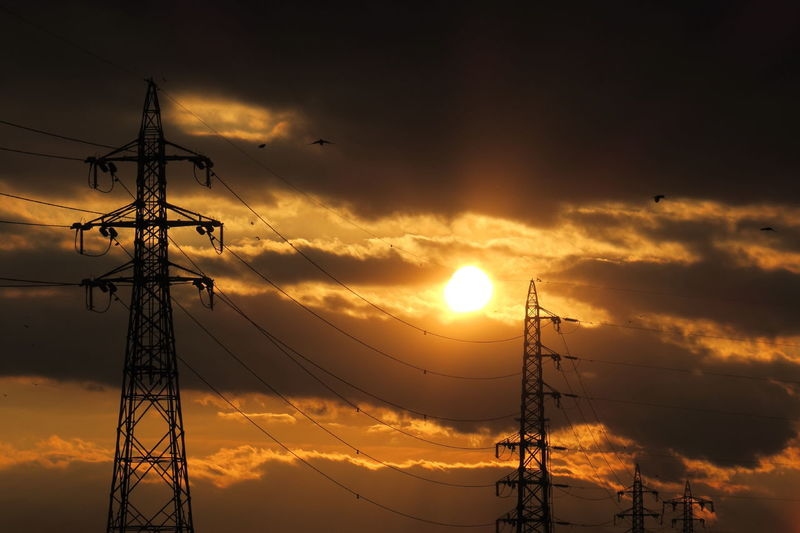 High Section Of Electricity Pylons Against Sunset
