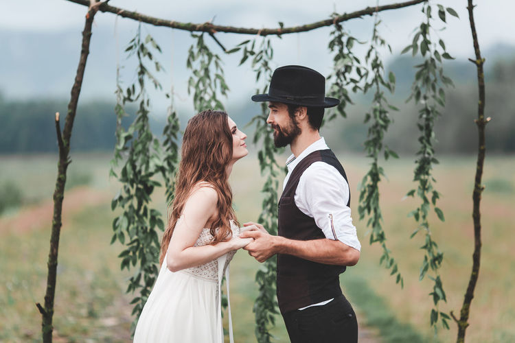 A loving couple at a wedding ceremony. Two people look at each other and hold hands. They are happy. She is wearing a white wedding dress, he wears a black hat, a shirt and pants with suspenders. Both are young and beautiful. They have attractive looks6 beautiful faces and slender figures. The girl has long hair, the guy wears a beard. In the background a wedding arch from plants. Photo taken in nature with daylight. Fashion Nature Wedding Bonding Bride Couple - Relationship Emotion Event Love Men Newlywed Outdoors People Portrait Positive Emotion Real People Togetherness Two People Wedding Wedding Dress Women Young Adult Young Couple Young Men Young Women