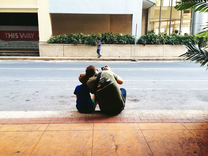 Rear view of father and son photographing while sitting on footpath by street