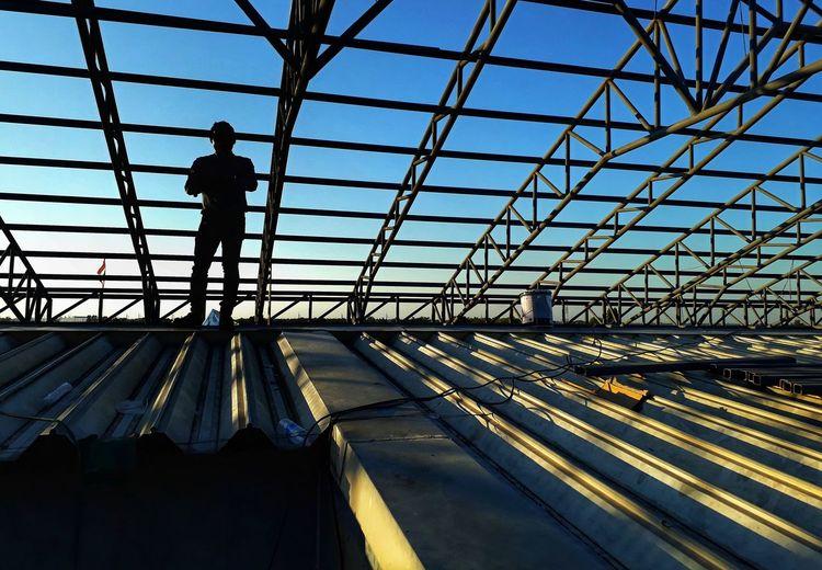 Man standing below metallic roof