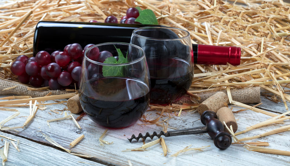 Close up view of drinking glasses filled with red wine, bottle and grapes plus corkscrew with straw and burlap on white rustic boards Celebration Merlot Red Wine Wood Alcohol Anniversary Bottle Close-up Corkscrew Drink Glass Grape Wine Wine Grapes
