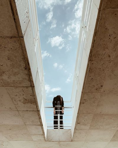 Low angle view of woman leaning on railing against sky