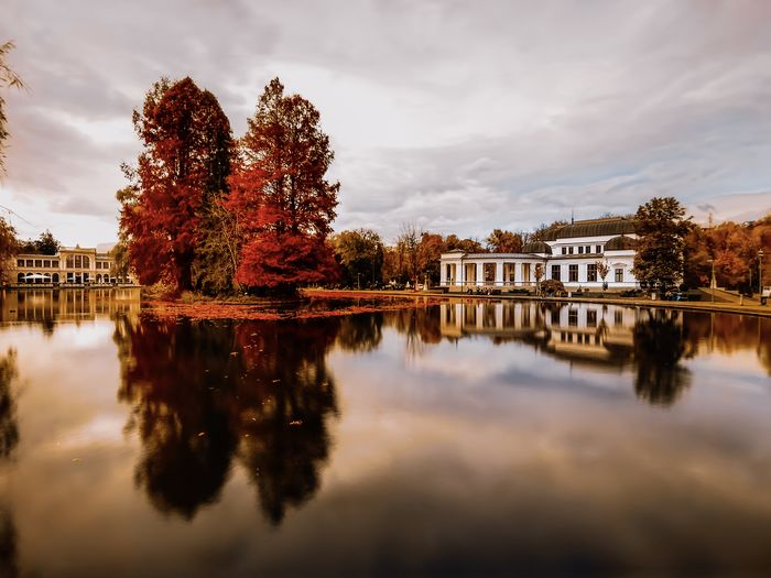 Reflection of trees and buildings in lake against sky