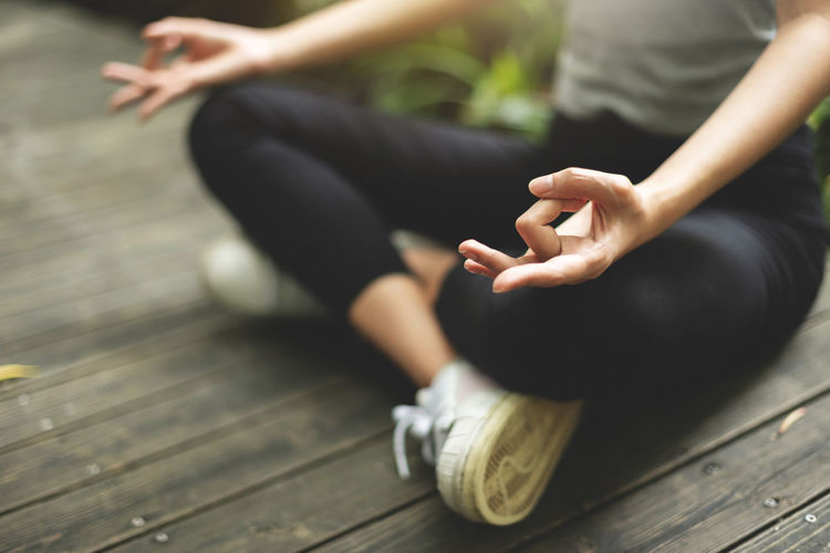 Low section of woman doing yoga on boardwalk