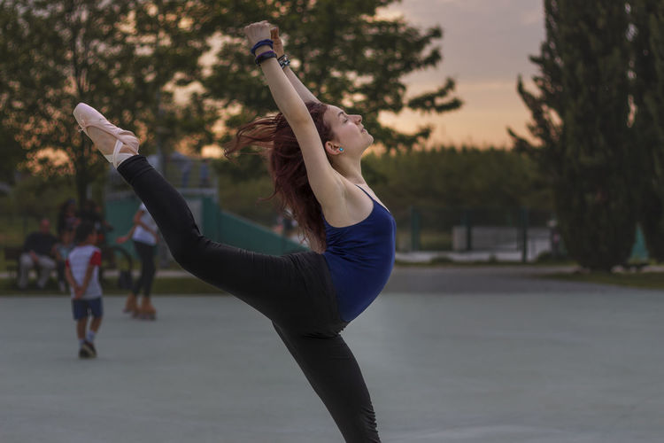 Side View Of Woman Dancing Ballet In Park During Sunset