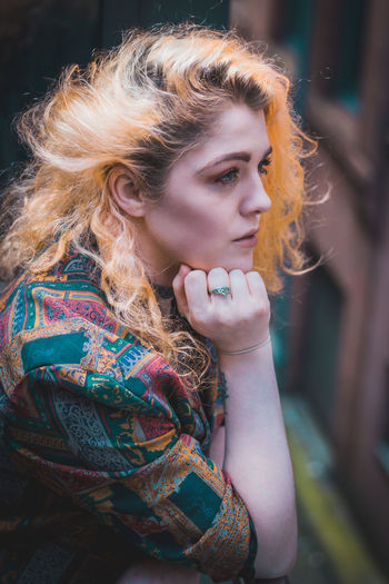 Close-up of thoughtful young woman with dyed hair