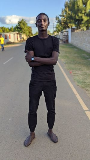 Portrait of young man standing on road