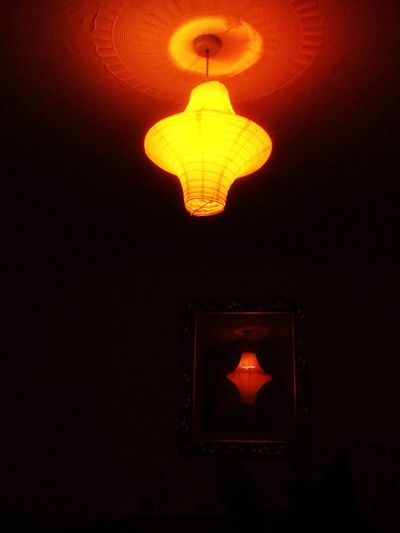 Low angle view of lit lamp hanging in dark room