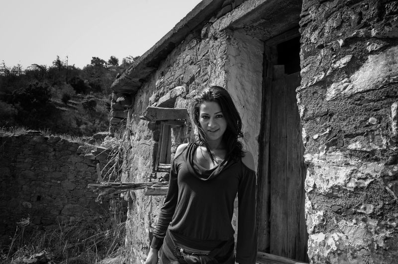 Portrait Of Young Woman Standing By Abandoned House