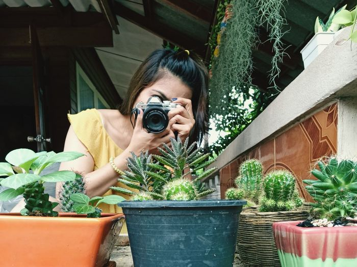 Woman taking photo small tree with camara with happiness.