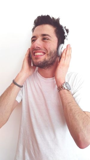 Happy Man Listening To Music Against Wall