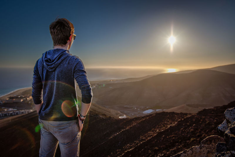 Rear view of man standing on mountain at sunset