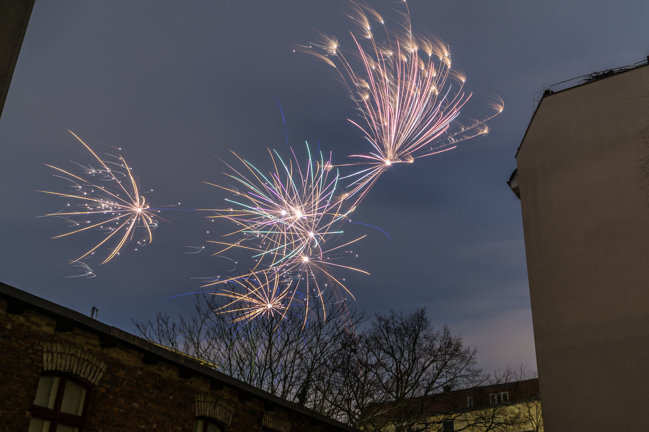 low angle view, firework display, firework - man made object, long exposure, night, celebration, sky, exploding, illuminated, built structure, architecture, motion, arts culture and entertainment, building exterior, no people, blurred motion, event, outdoors, firework