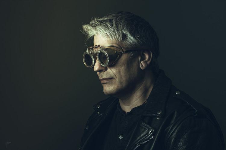 Portrait of man wearing sunglasses against black background