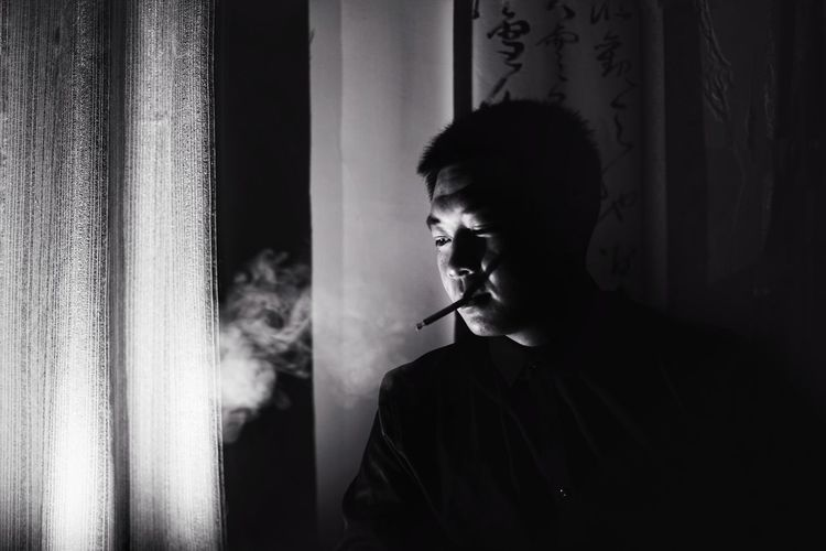 Casual Clothing Cigarette  Contemplation Curtain Hairstyle Headshot Home Interior Indoors  Leisure Activity Lifestyles Looking One Person Portrait Real People Smoking - Activity Smoking Issues Standing Waist Up Window Young Adult Capture Tomorrow