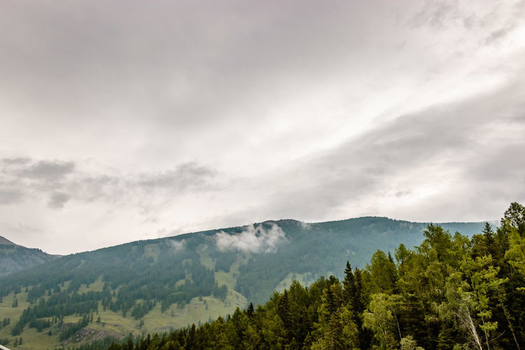 Scenic View Of Mountains Against Gloomy Sky