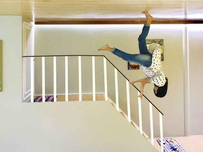 Full length of boy jumping on staircase at home