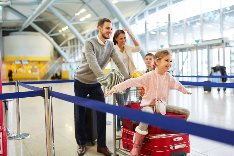 Happy family pushing girl sitting on luggage cart at airport