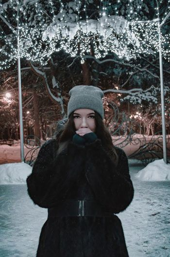 Portrait of young woman standing by tree during winter